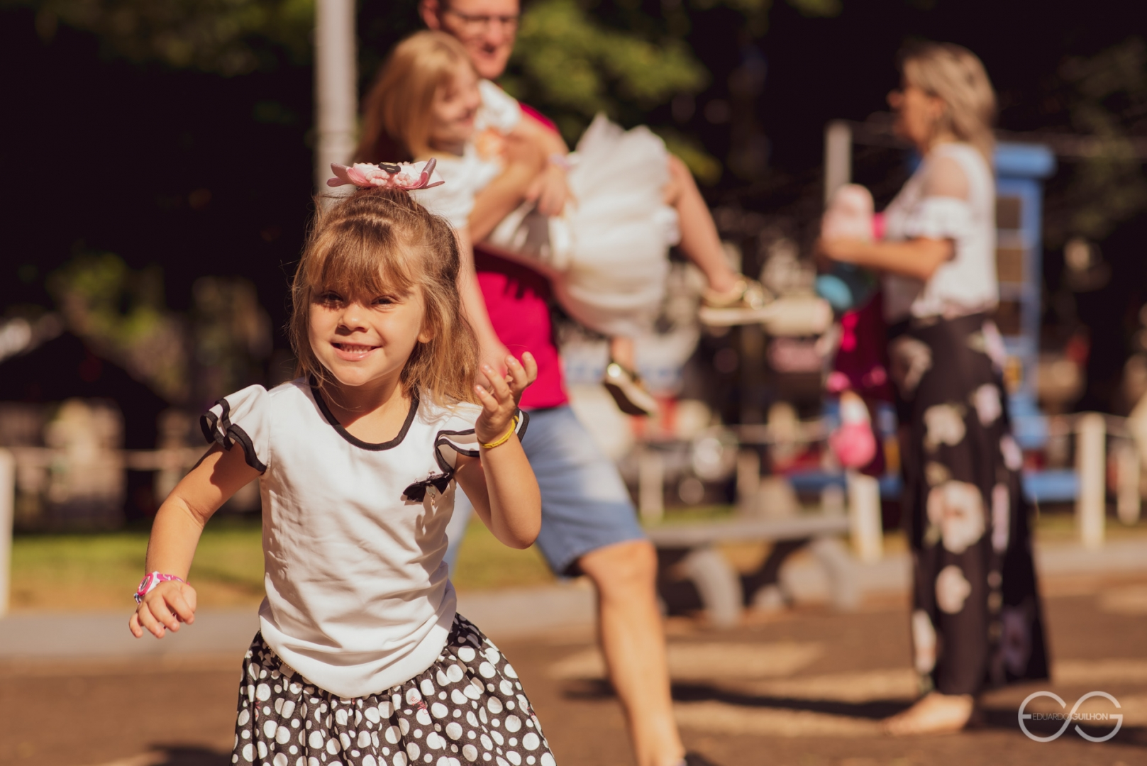 Amanda correndo para ver a foto e ao fundo os pais brincando com a Kelly