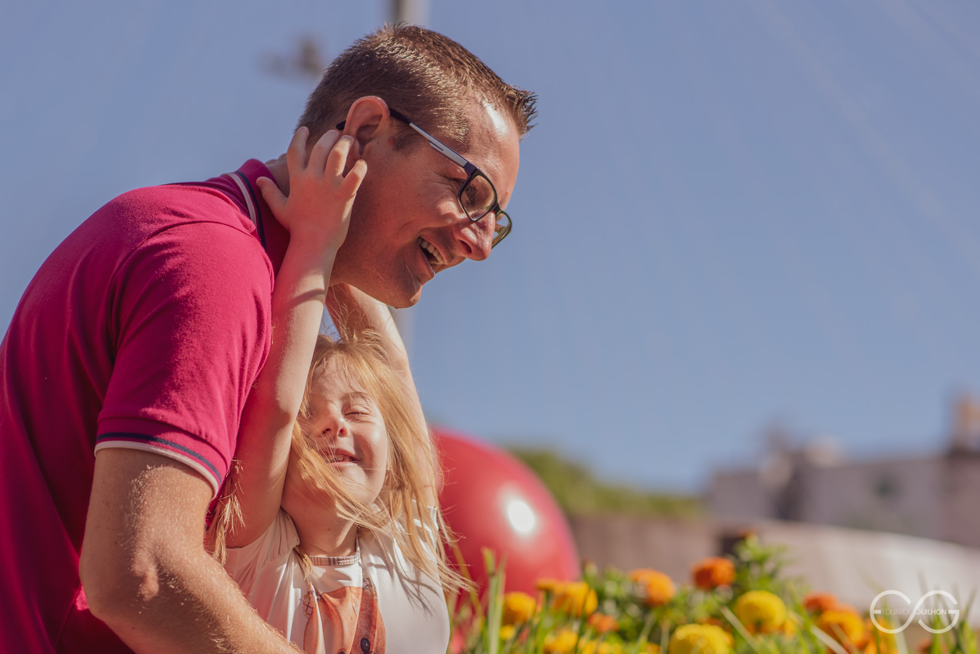 Kelly pendurada no pescoço do pai com a felicidade do roso